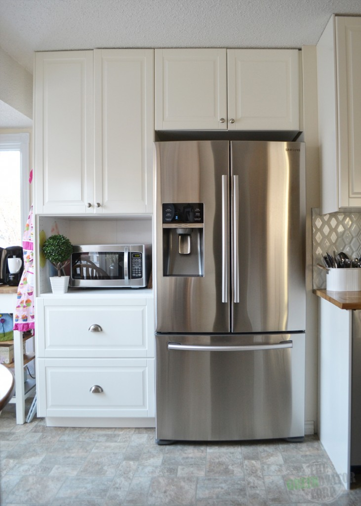 A bright white Ikea galley kitchen renovation with butcher block counters, hexagon tiles, stainless steel appliances.